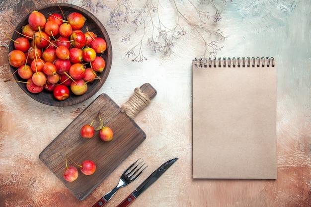 Вид сверху ягод вишни на кухонной доске, миске с вишней, вилкой, ножом, ноутбуком