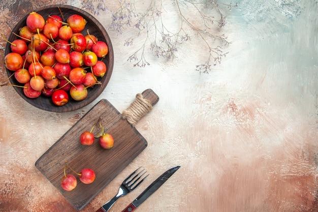 Вид сверху ягод вишни на кухонной доске, миске из веток вишни, вилки, ножа