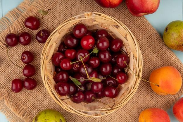 かごの中のさくらんぼと梨アプリコット桃さくらんぼ青背景の荒布のパターンの上面図