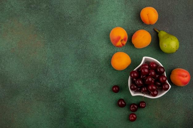 Вид сверху вишни в миске и узор из абрикосов, вишен и груш на зеленом фоне с копией пространства