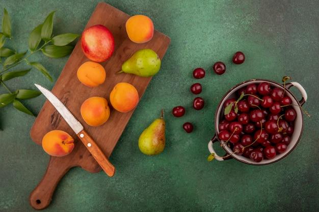 Вид сверху вишни в миске и узор из абрикосов, груши, персика, с ножом на разделочной доске и листьями на зеленом фоне