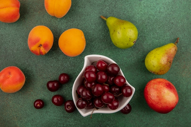 Вид сверху вишни в миске и узор из абрикосов, груш, вишен на зеленом фоне
