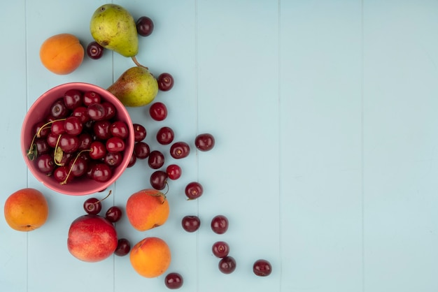 Вид сверху вишни в миске и узор персика, абрикоса, груши, вишни на синем фоне с копией пространства