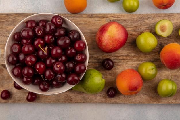 Вид сверху вишни в миске и узор из персика и сливы абрикоса на разделочной доске и на белом фоне