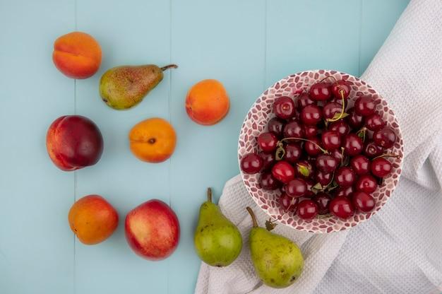 Вид сверху вишни в миске на белой ткани и узор из персикового грушевого абрикоса на синем фоне