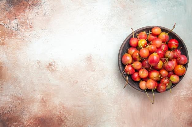 さくらんぼの上面図テーブルの上のボウルに食欲をそそるさくらんぼ