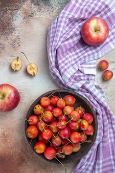 さくらんぼの上面図市松模様のテーブルクロスのボウルに2つのりんごさくらんぼ
