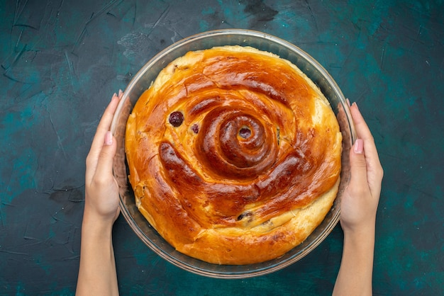 チェリーケーキの上面図は、紺色のケーキの甘い焼きフルーツの暗闇の中で女性によって保持されています