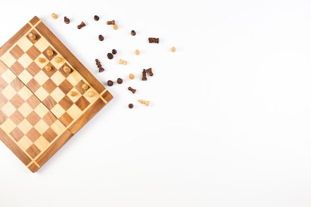 Вид сверху шахматной доски с шахматными фигурами на белом