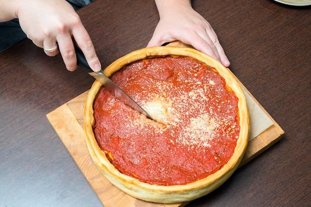 시카고 피자의 상위 뷰입니다. 토마토 소스와 쇠고기를 곁들인 시카고 스타일의 딥디쉬 이탈리아 치즈 피자를 손으로 자르는 여성