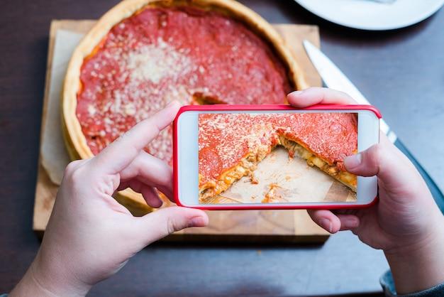 시카고 피자의 상위 뷰-시카고 스타일 딥 디쉬 이탈리아 치즈 피자의 스마트 폰으로 사진을 찍는 여자 손.