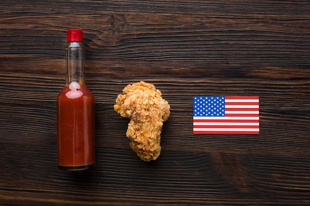 Вид сверху курица и бутылка соуса