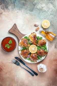 보드 마늘 오일 소스 포크 나이프에 레몬 허브 양파와 치킨 치킨의 상위 뷰