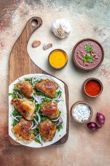 Вид сверху курицы, чеснока, лука, курицы с зеленью на соусе из лаваша с красочными специями