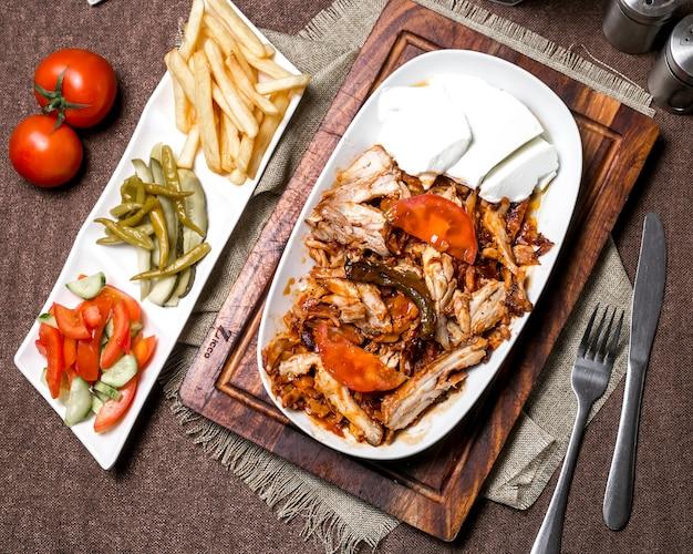 チキンケバブとトマトソースの平面図、ヨーグルトポテトのピクルスと野菜添え