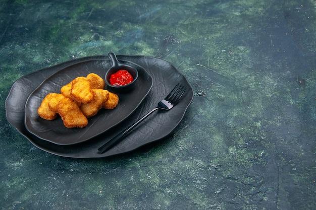 어두운 표면의 오른쪽에 검은 접시에 치킨 너겟과 케첩 포크의 상위 뷰