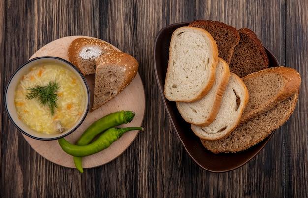 ボウルに鶏肉のオルゾスープとまな板の上の唐辛子、木製の背景にボウルに茶色の穂軸白とライ麦パンのスライスをシードした上面図