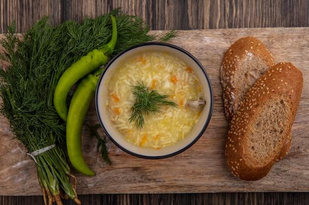 Вид сверху куриного супа орзо в миске и засеянных ломтиками черного хлеба с укропом и перцем на разделочной доске на деревянном фоне