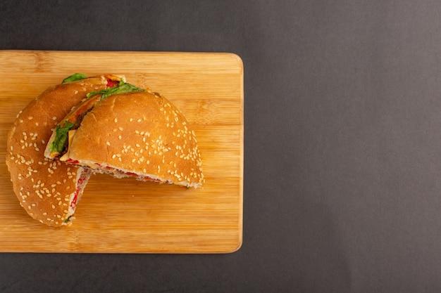 Вид сверху куриного сэндвича с зеленым салатом и овощами внутри, нарезанными половинками на деревянной поверхности
