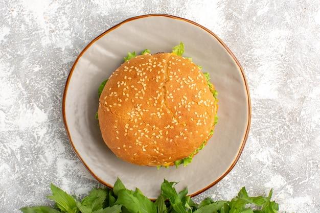 明るい表面のプレートの内側にグリーンサラダと野菜とチキンサンドイッチの上面図