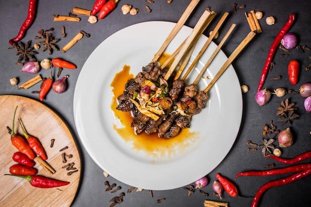 Вид сверху куриного сатайского блюда на белой тарелке и черном фоне