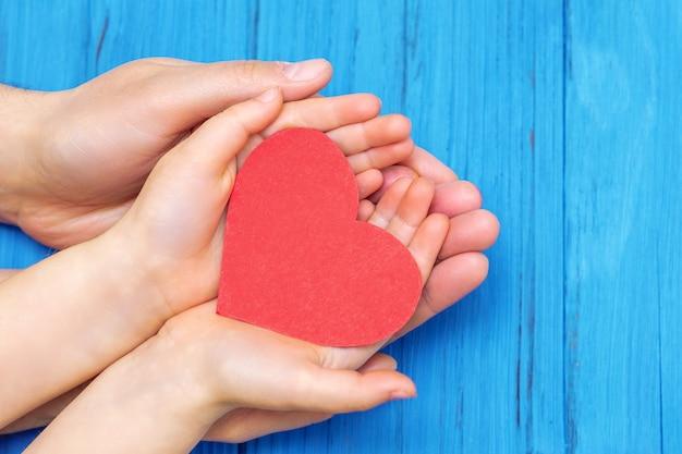 紙の赤いハートを保持している子供とお父さんの手の上面図。家族と家族関係の概念。