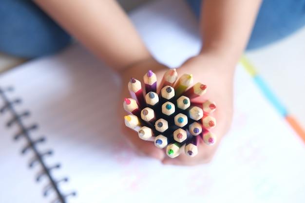 Взгляд сверху девушки ребенка держа много карандашей цвета.