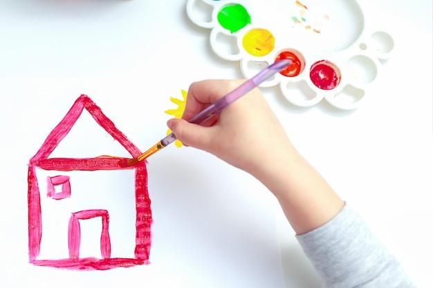 Вид сверху детской руки с карандашом рисует изображение красного дома на белой бумаге.