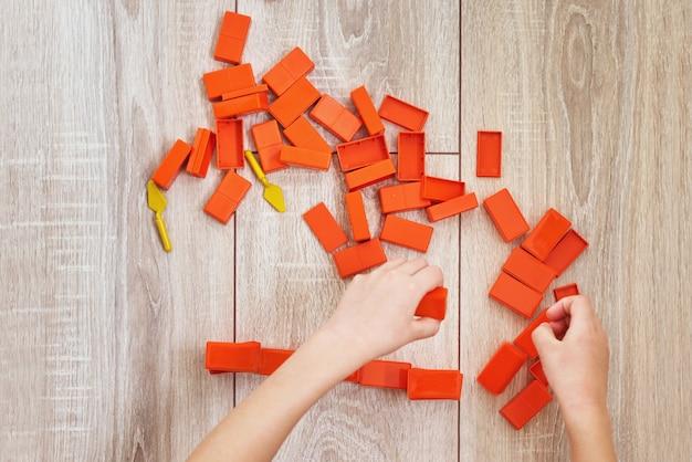 Взгляд сверху рук ребенка играя с оранжевыми кирпичами игрушки. концепция детей lerning и образования. детский досуг с развивающими игрушками