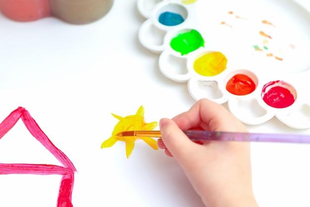 Вид сверху ребенка рисует солнце и красный дом акварелью на белом листе бумаги.