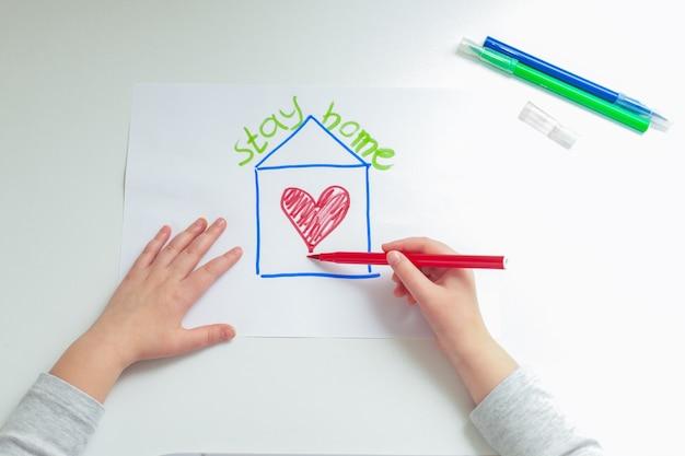 自宅の白い紙にフェルトペンで塗られた家でハートを描く子供の手の上面図。家にいるコンセプト。