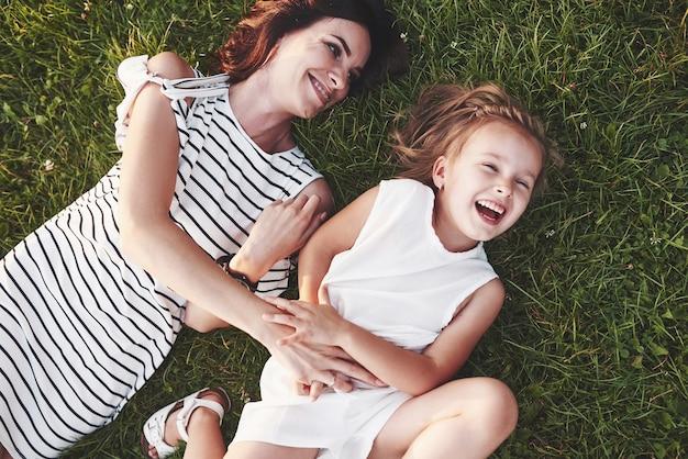 日差しに満ちた芝生に横になり、お互いを見つめる子供と母親の平面図