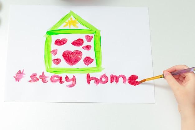 집에서 흰색 종이에 수채색 브러시로 하트가 있는 페인트 칠한 집 아래에 있는 어린이 손으로 집에 머무르는 단어를 그리는 상위 뷰.