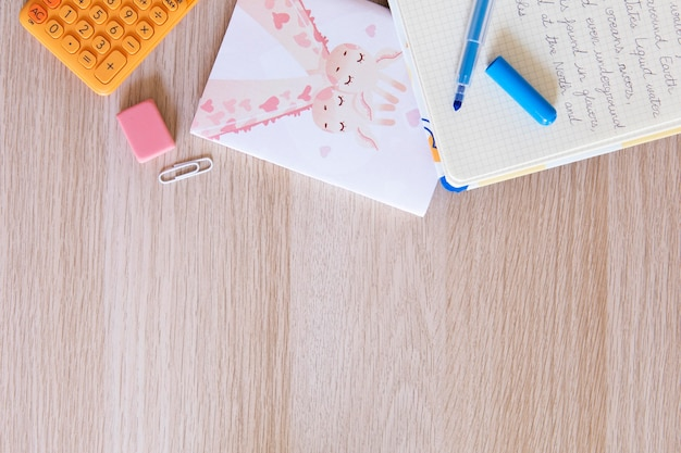 Вид сверху на детский стол с блокнотом и ручкой