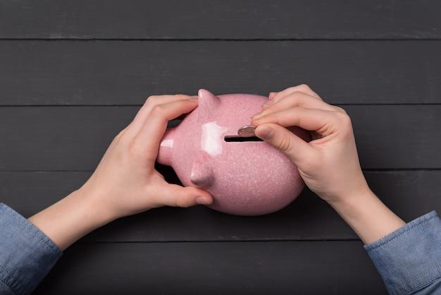 자녀의 손의 상위 뷰는 돼지 저금통 동전에 넣습니다. 저축 돈 개념