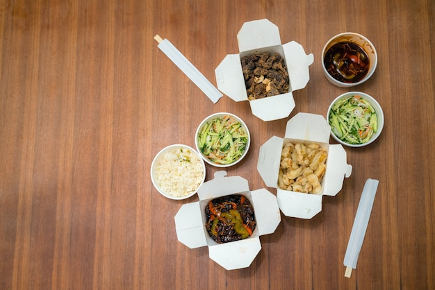 中国の上面図は、木製のテーブルに箸で食べ物を持ち帰ります。白い箱の中のスパイシーなアジア料理