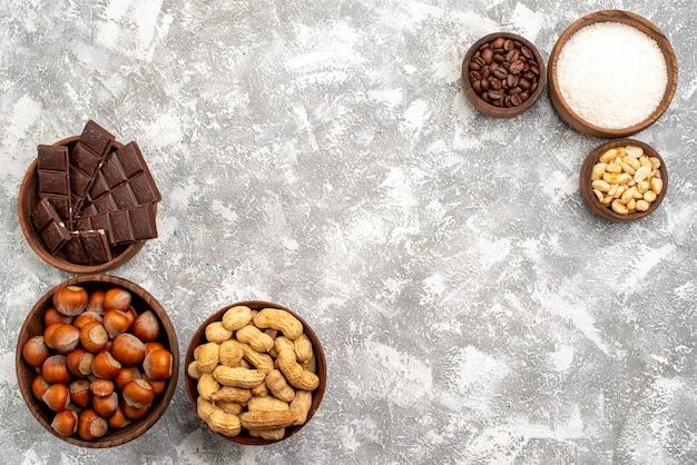 Вид сверху шоколадных батончиков с фундуком и арахисом на белой поверхности