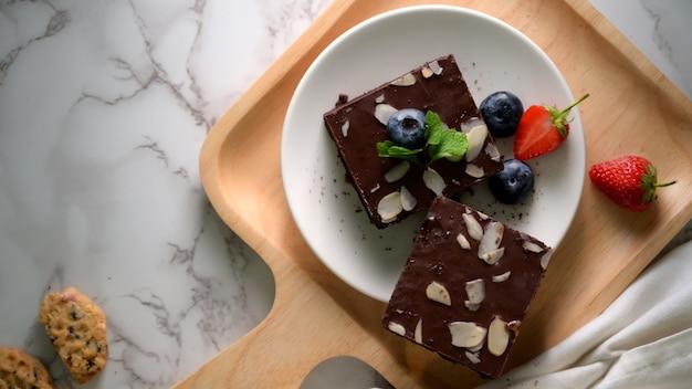 上のミントの葉と白いプレート上のチョコレートブラウニーのトップビュー
