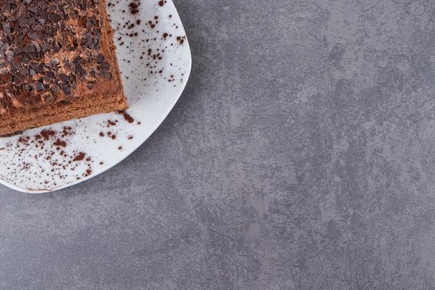 회색 표면 위에 접시에 초콜릿 케이크의 상위 뷰