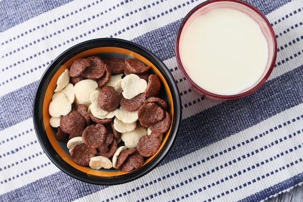 ボウルにチョコレートコーンフレークとテーブルの上の牛乳のガラスの上面図