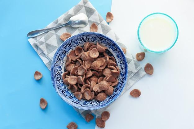 色の背景のボウルにチョコレートコーンフレークの上面図