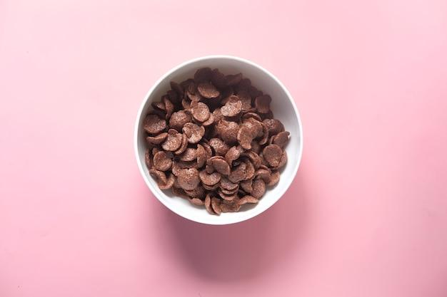 Вид сверху шоколадных кукурузных хлопьев в миске на розовом.