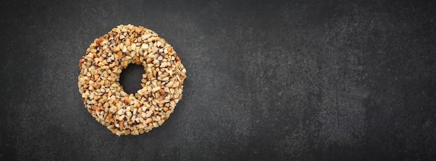 ダークグレー、グレー、黒のトーンのテクスチャ背景にピーナッツをトッピングしたチョコレートドーナツの上面図とテキストのコピースペース