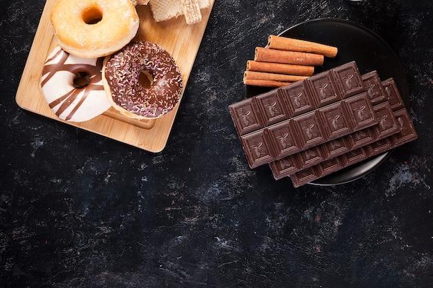 ダークウッドのヴィンテージの背景にチョコレート、ドーナツ、その他のお菓子の上面図
