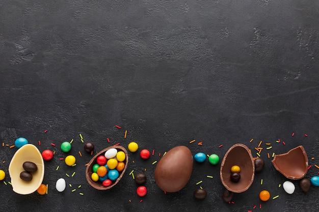 Вид сверху шоколадных пасхальных яиц, наполненных разноцветными конфетами