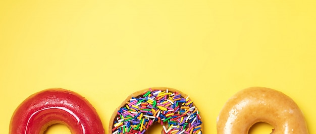 振りかけるとチョコレートのフロストドーナツの平面図、黄色の背景に砂糖を艶をかけたフロストとイチゴの艶をかけられたドーナツ。