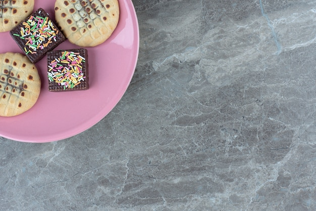 핑크 접시에 초콜릿 웨이퍼와 쿠키의 상위 뷰.