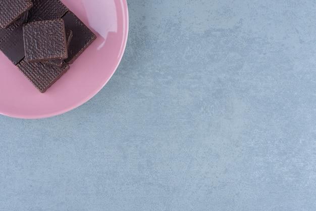 ピンクのプレート上のチョコレートウエハースの上面図。写真の隅に。