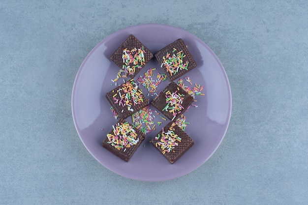 Вид сверху шоколадных вафель на фиолетовой пластине.