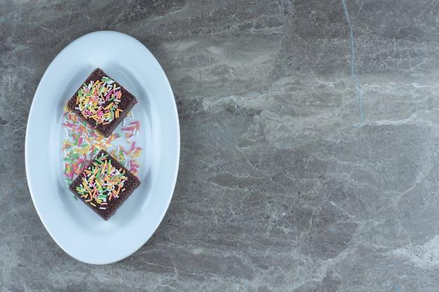 白いプレートに振りかけるチョコレートウエハースの上面図。